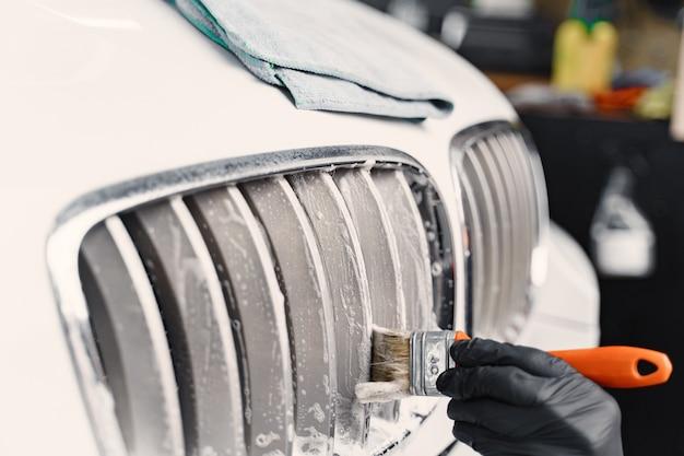Мужская рука с губкой из пенопласта для мытья машины Бесплатные Фотографии