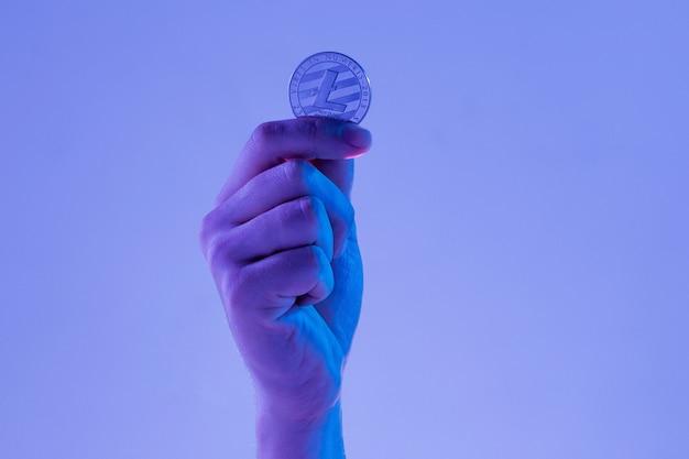Мужская рука с золотым litecoin на синем фоне Бесплатные Фотографии