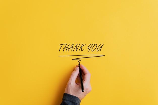 感謝サインを書く男性の手 Premium写真
