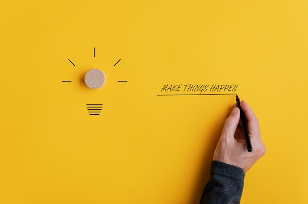Male hand writing a make things happen sign next to a light bulb shape over yellow Premium Photo