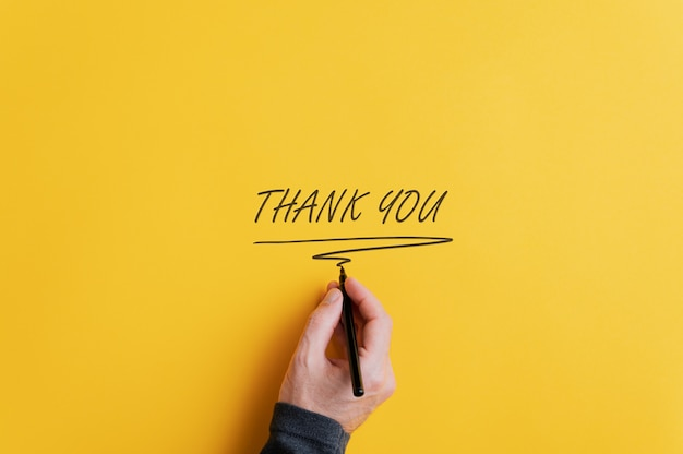 Male hand writing a thank you sign Premium Photo