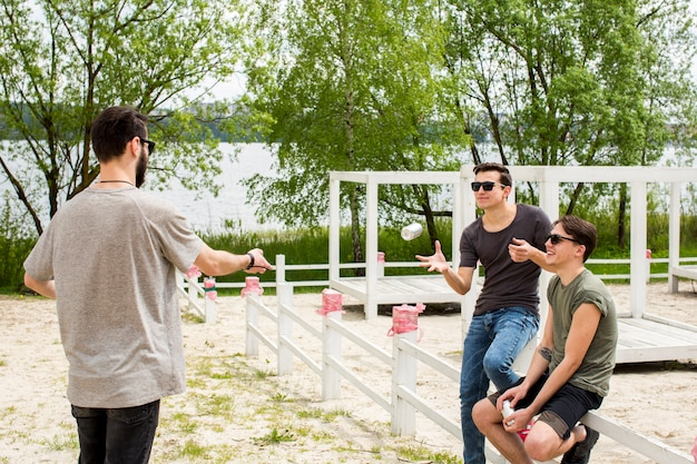 Male handing beer to friends Free Photo