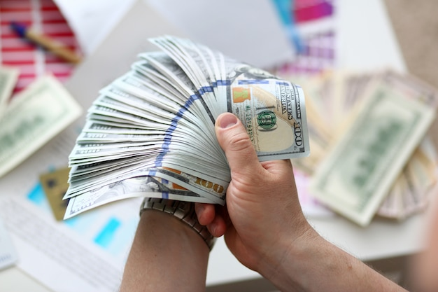 Male hands counting money from huge pack Premium Photo