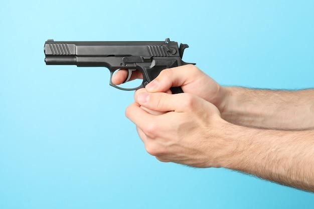 Мужские руки держат черный пистолет на синем Premium Фотографии