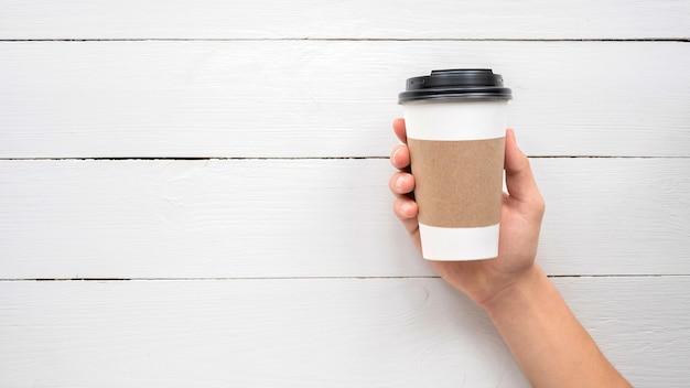 재활용 커피 컵을 들고 남자 손입니다. 재활용 아이디어 무료 사진