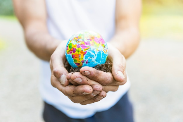 Male hands holding small globe Free Photo