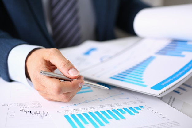 Male hands holds documents with financial statistics at office workspace closeup. Premium Photo