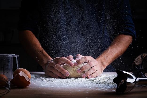 Male hands making dough for pizza, dumplings or bread. baking concept. Premium Photo