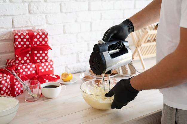 キッチンのクローズアップで生地と電気ミキサーを混合する男性の手 Premium写真