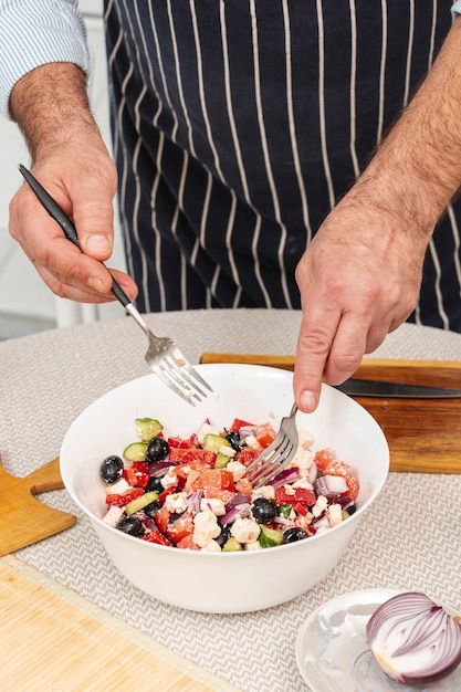 Male hands mixing a tasty salad Free Photo