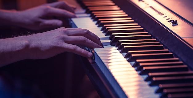 男性の手は美しいカラフルな背景、音楽活動の概念のピアノの鍵盤のクローズアップ 無料写真