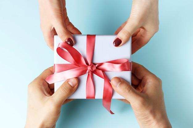 Male hands passes gift box to female hands Premium Photo