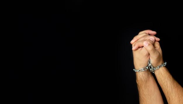 Мужские руки связали цепью на темном фоне. концепция зависимости людей Premium Фотографии