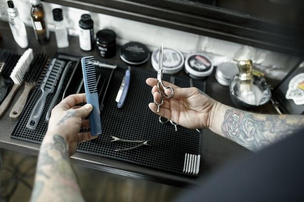 Mani maschili e strumenti per tagliare la barba al negozio di barbiere. strumenti d'epoca del negozio di barbiere. Foto Gratuite