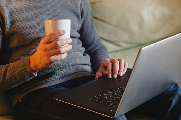 Male hands using laptop at home Premium Photo