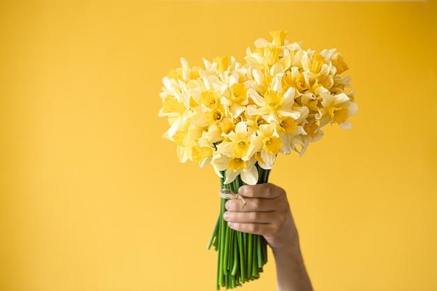 黄色い水仙の花束を持つ男性の手。 無料写真