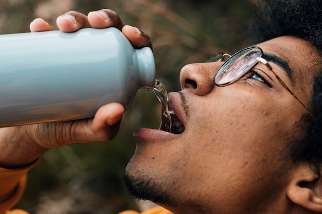 Male hiker face wearing eyeglasses drinking the water from bottle Free Photo