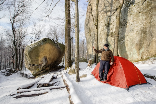 Male hiker nearly his red tent in the mountains Premium Photo