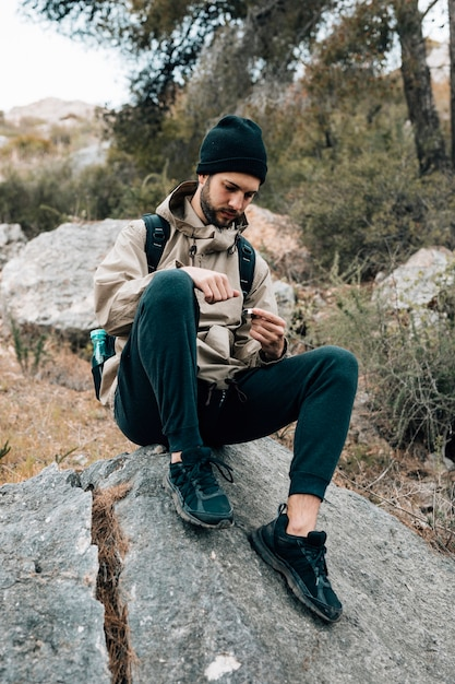 A male hiker sitting on rock looking at navigation compass Free Photo