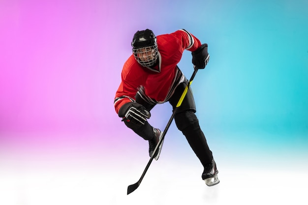 Male hockey player with the stick on ice court and neon gradient space Free Photo