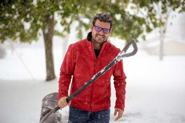 Мужчина держит снежную лопату и одет в красную куртку во время улыбки Бесплатные Фотографии