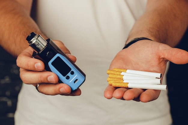 Male holding cigarettes and vape inhaler close up photo Premium Photo