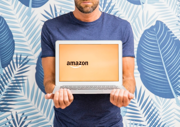 Male holding laptop with amazon site Free Photo