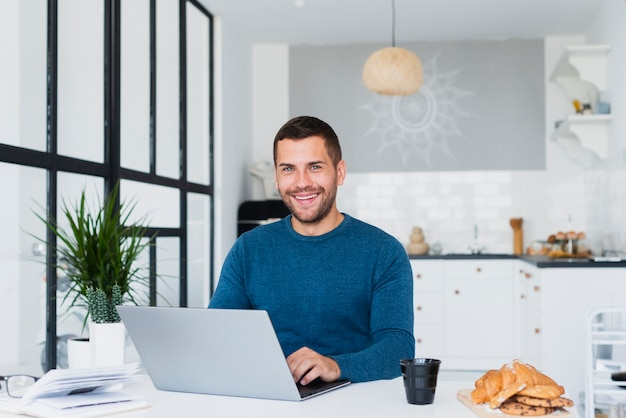 Male at home using laptop mock-up Free Photo