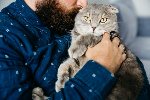 Male hugging adorable cat Free Photo