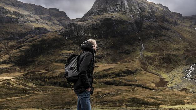 Парень в рюкзаке и теплом пальто гуляет по горной местности шотландии под серым небом Бесплатные Фотографии