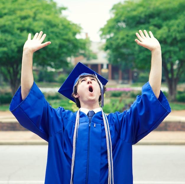 卒業後の自由を楽しんでいる青いマントの男性 無料写真