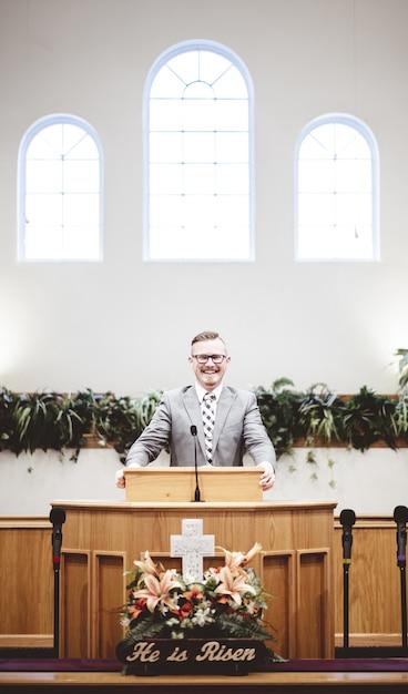 Мужчина в официальной одежде проповедует библию с трибуны у алтаря церкви Бесплатные Фотографии