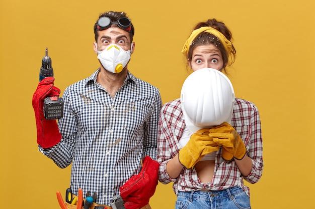 Мужчина в защитной маске стоит с дрелью, а женщина прячется под белым шлемом, обновляя свою квартиру, работая вместе с использованием строительных инструментов. строители улучшают что-то в комнате Бесплатные Фотографии