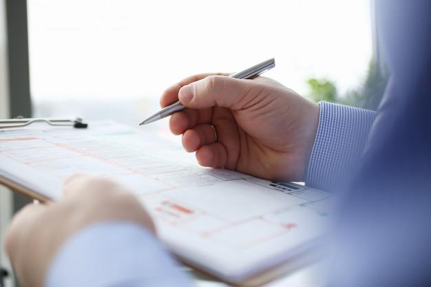 男性の保険者の手がシルバーペン事故を保持します。 Premium写真