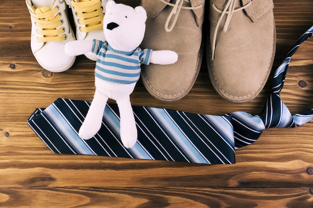 Male and kid boots near tie with soft toy Free Photo