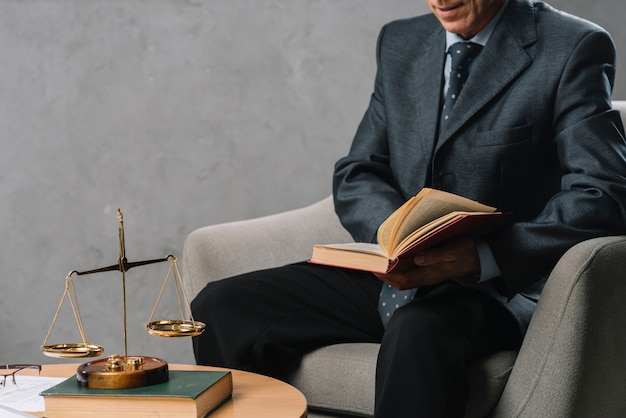 Male lawyer holding law book sitting in the office with justice scale on table Free Photo