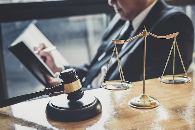 Male lawyer or judge working with contract papers, law books and wooden gavel on table in courtroom Premium Photo