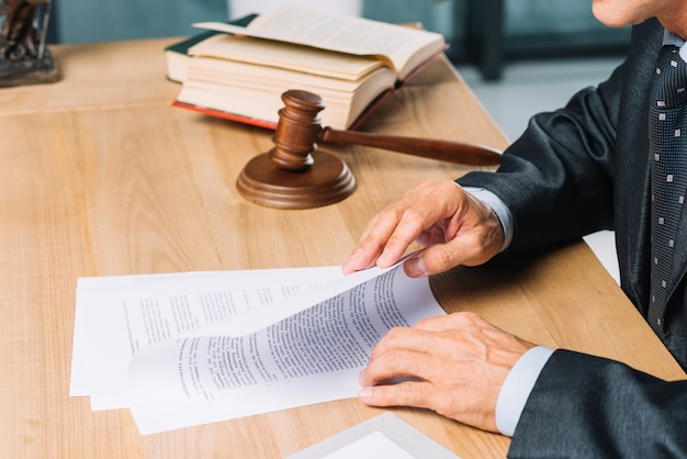 Male lawyer reading documents on wooden desk Free Photo