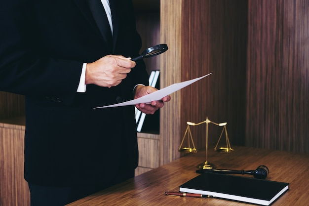 Male lawyer reading legal contract agreement and examining documents Premium Photo