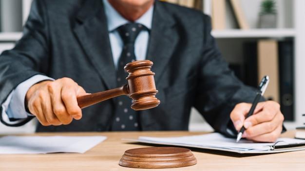 Мужской адвокат, пишущий на документе в зале суда, дающий вердикт, ударяя молотком по молотку Premium Фотографии