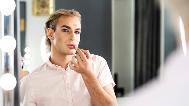 Male make-up look looking in the mirror Free Photo