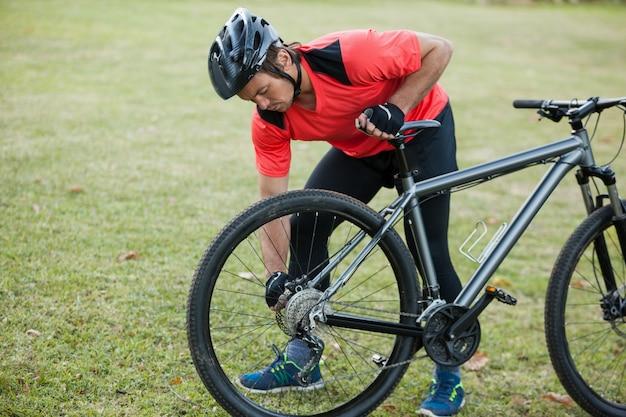 Мужчина горный байкер чинит велосипедную цепь Premium Фотографии