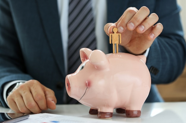 Male manager putting small wooden human figure into piggybank close-up Premium Photo