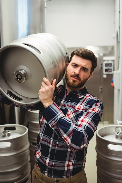 Male manufacturer carrying keg in brewery Premium Photo