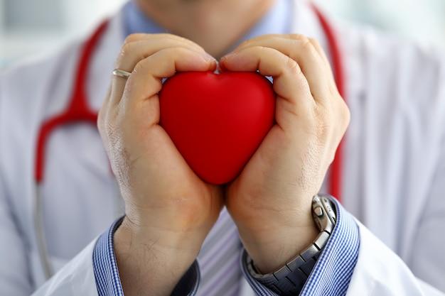 男性医学医師の手を保持し、赤いおもちゃの心をカバー Premium写真