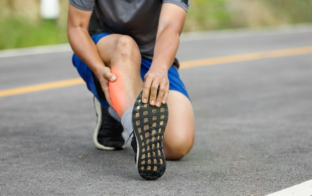 Male middle aged having a cramp while jogging. stop and massage calf Premium Photo
