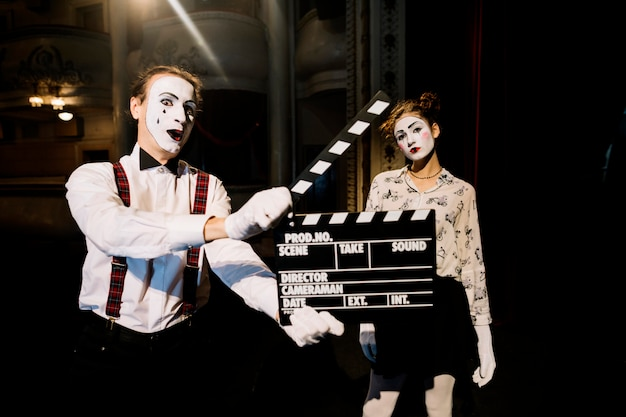Male mime artist holding clapperboard in front of female mime artist Free Photo