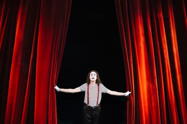 赤いカーテンの近くの舞台で演じる男性ママのアーティスト Premium写真