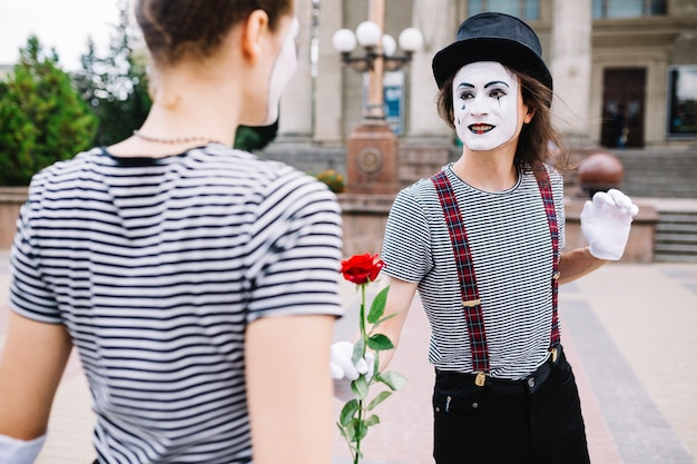 Male mime giving rose to female mime Free Photo