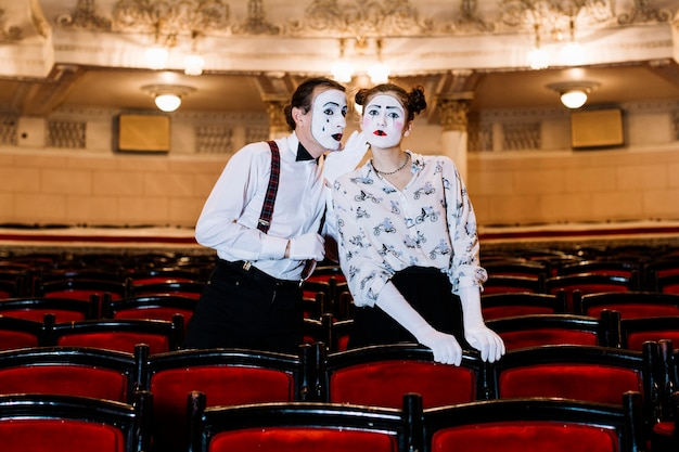 Male mime whispering in female mime's ear standing among chair Free Photo